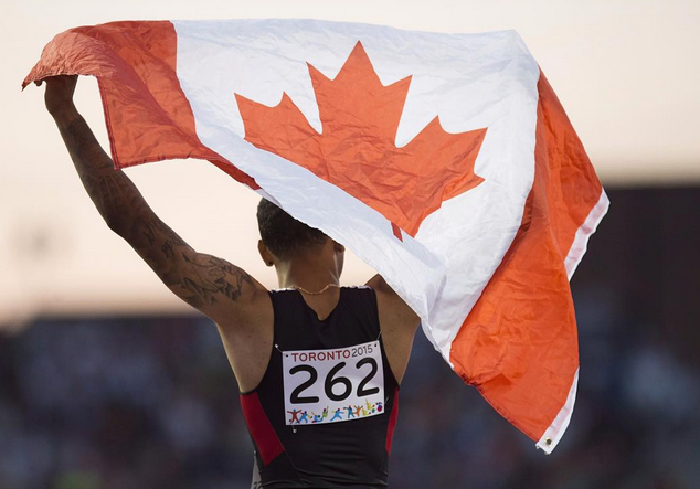 Canadian athlete holding up Canadian flag at Toronto 2015 Pan Am Games
