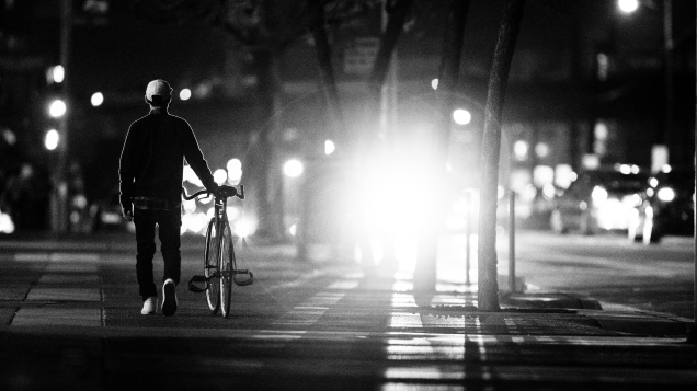Cyclist walking bike on street at night